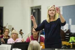 Gina Provenzano conducts the Midland Community Orchestra during a rehearsal on Monday, Oct. 23, 2017 at Midland High School. (Katy Kildee/kkildee@mdn.net)