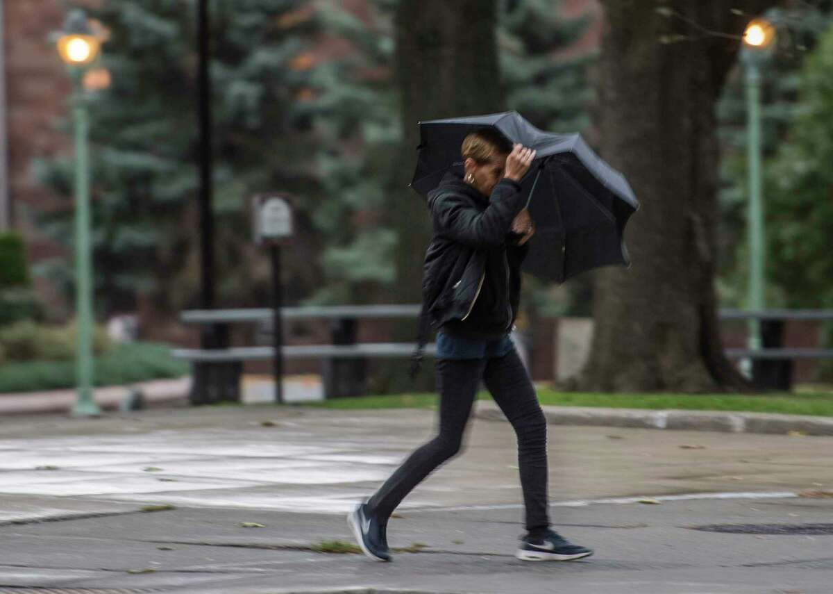 A pedestrian walks near Academy Park holding on to her umbrella in the high winds and rain that came to the area Tuesday Oct. 24, 2017 in Albany, N.Y. High winds will hit the Capital Region starting Sunday night, Feb. 24, 2019. (Skip Dickstein/Times Union)