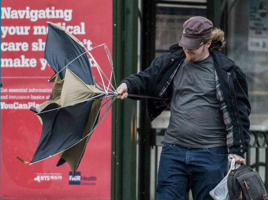 A commuter left the bus and opened his umbrella on State Street and it lost it's shape in the high winds and rain that came to the area Tuesday Oct. 24, 2017  in Albany, N.Y.    (Skip Dickstein/Times Union) Photo: SKIP DICKSTEIN, Albany Times Union