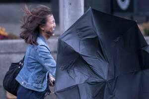 A commuter walks down Washington Avenue as her umbrella loses it shape in the high winds and rain that came to the area Tuesday Oct. 24, 2017  in Albany, N.Y.    (Skip Dickstein/Times Union)