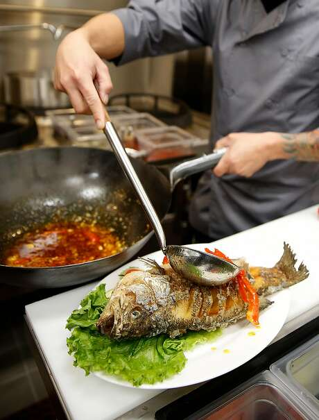 Sauce is poured over black bass after fish was deep fried to make Pla Sam Ros--a sweet and sour black sea bass with crispy basil leaves, a Northeastern Thai dish--made by chef Chanon Hutasingh at Esan on Wednesday, August 30, 2017, in San Francisco, Calif. Photo: Liz Hafalia, The Chronicle