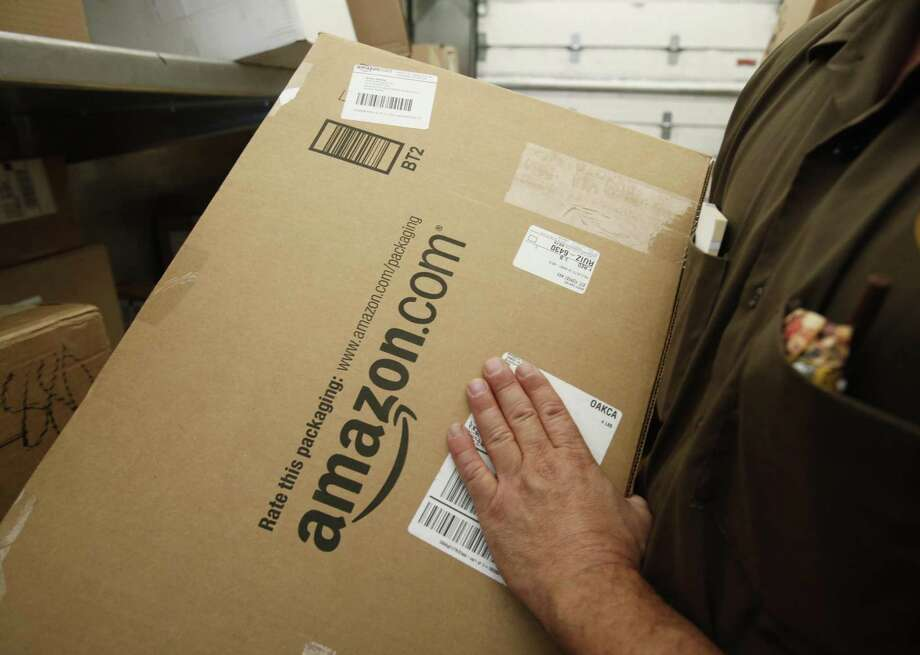 A United Parcel Service driver delivers an Amazon.com box in Palo Alto, Calif. Amazon has launched Business Prime Shipping, available in the U.S. and Germany. It offers free two-day delivery to companies paying $499 to as much as $10,099 a year depending on their size, Amazon said. Photo: Paul Sakuma /Associated Press / AP
