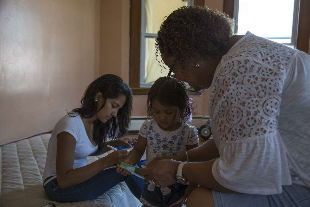 Community health worker Milagrosa Seguinot entertains Madeley, 2, while mother Dunia Lizeth Robles Navarro fills out health care forms in their Bridgeport home. Seguinot, who has been involved in community health for more than 25 years, provides residents with information and reading materials in Spanish.