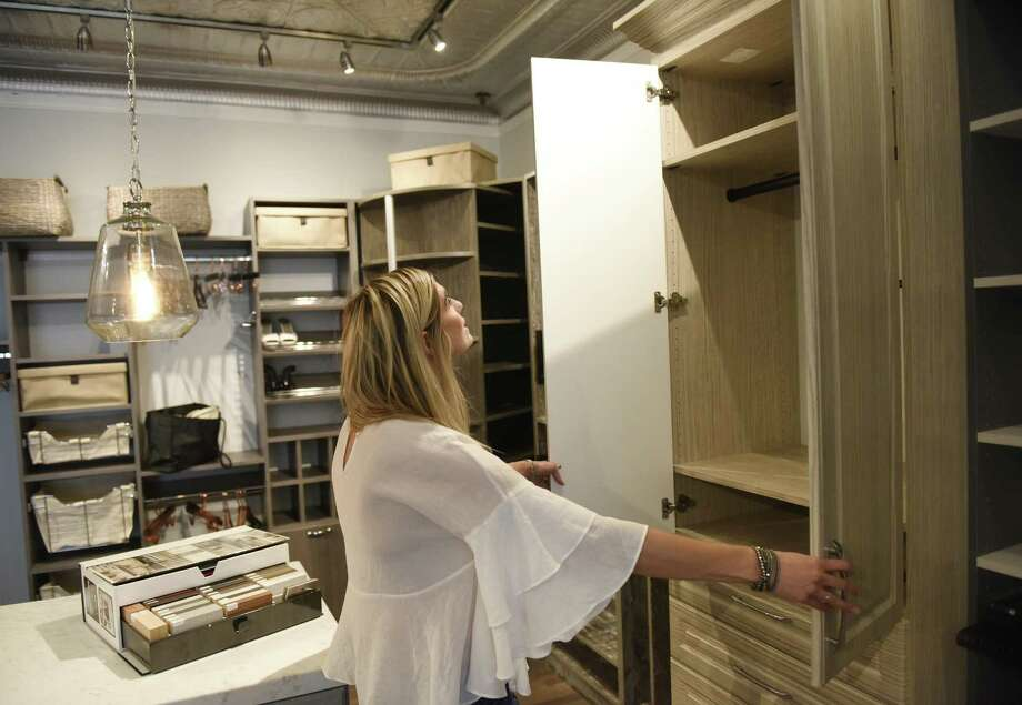 Store manager Erin Hardie opens a cabinet at Closets and More in the Cos Cob section of Greenwich, Conn. Thursday, Oct. 5, 2017. Photo: Tyler Sizemore / Hearst Connecticut Media / Greenwich Time