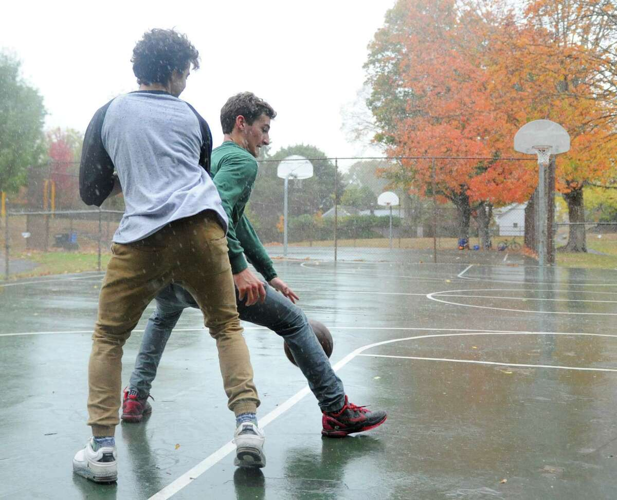 Riverside residents Thomas Hickman, left, and Kevin Piortzkowski play basketball in the rain at the Bible Street Playground in the Cos Cob section of Greenwich, Conn. Tuesday, Oct. 24, 2017.