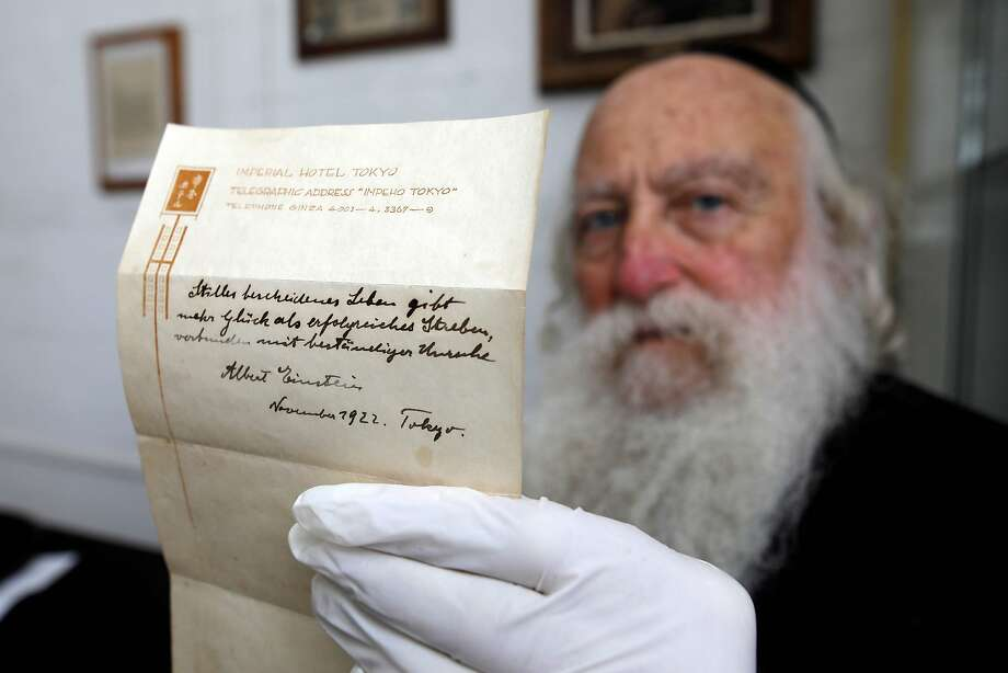 This file photo taken on October 19, 2017 shows an Ultra-Orthodox Jewish man displaying one of two notes written by Albert Einstein, in 1922, on hotel stationary from the Imperial Hotel in Tokyo Japan, at the Winner's auction house in Jerusalem.  The note that Albert Einstein gave to a courier in Tokyo briefly describing his theory on happy living sold at auction in Jerusalem on October 24, 2017 for $1.56 million, the auction house said.  Photo: MENAHEM KAHANA, AFP/Getty Images