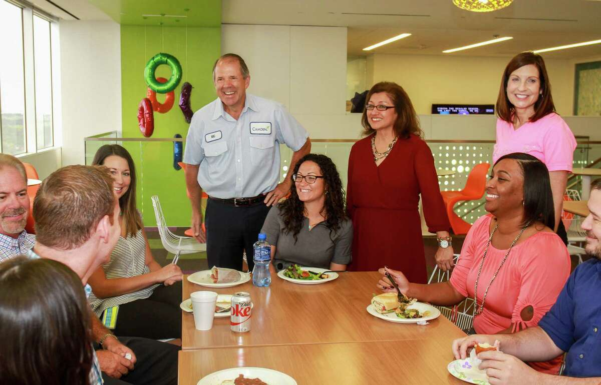 CEO and chairman Ric Campo, standing from left, Brenda Esparza, executive assistant human resources, and Cindy Sharringhausen, senior vice president human resources, visit with staff members having lunch at the Camden Cafe, at Camden Property Trust headquarters at 11 Greenway Plaza. (For the Chronicle/Gary Fountain, October 9, 2017)
