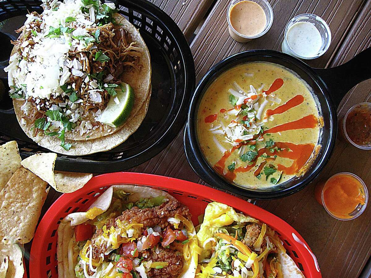 Green chile pork taco, upper left, green chile queso, a Dirty Sanchez taco and a Trashy Trailer Park taco from Torchy's Tacos on East Basse Road. The Austin-based chain is opening a second San Antonio location at The Rim.