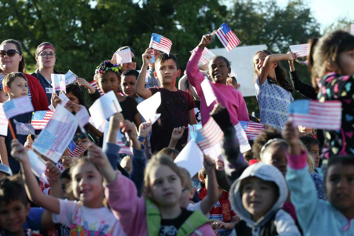 Children wave U.S. flags during the Parade of Nations at Colonies North Elementary School in 2017. The school has a long history of serving refugees from around the world. Research has shown that, nationally, much work needs to be done to improve education for English Language Learners.