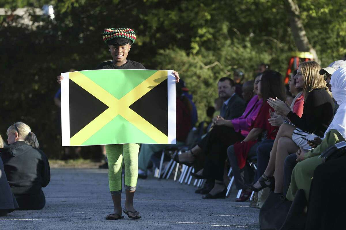 Cienna Black, 9, carries the Jamaican flag during the Parade of Nations at Colonies North Elementary School, Tuesday, Oct. 24, 2017. Forty nations were represented in the parade.