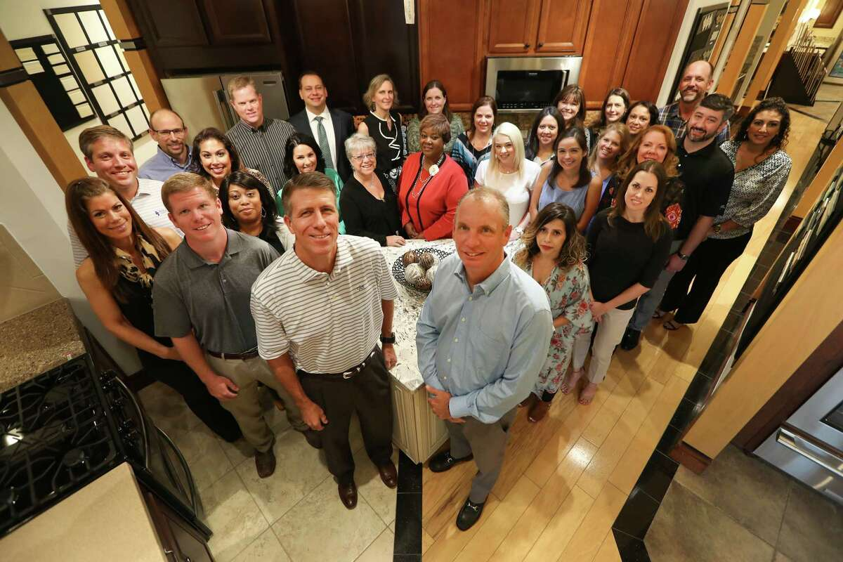 Newmark Homes President Mike Moody, left foreground, Vice President Jeff Dye, right, and their management team.
