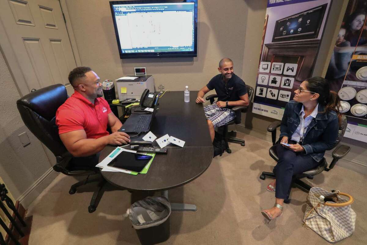 Newmark Homes Technical Consultant Brandon Hatton (left) show Nikhil and Salon Patel lighting options Wednesday, Sept. 27, 2017, in Houston. Newmark Homes were selected one of the Houston Chronicle's Top Workplaces. ( Steve Gonzales / Houston Chronicle )