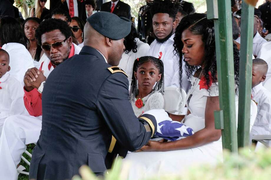 Myeshia Johnson Friday as she is presented with a folded US flag by a military honor guard member during the burial service for her husband US Army Sgt. La David Johnson at the Memorial Gardens East cemetery in Hollywood, Florida. The president's words following a call to the widow demonstrated anew his penchant for lying. Photo: GASTON DE CARDENAS /AFP /Getty Images / AFP or licensors