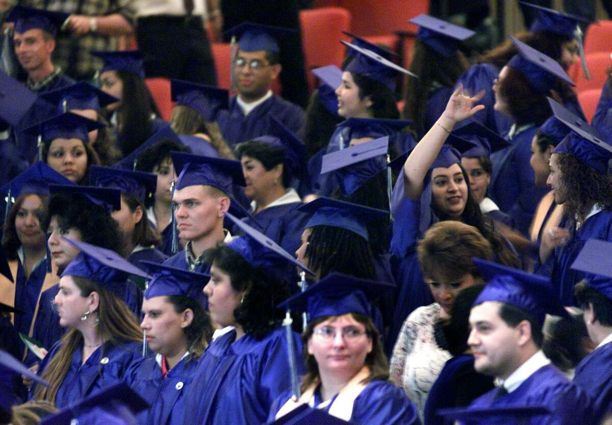 An unidentified Palo Alto College graduating student waves to the crowd as her classmates prepare for their commencement ceremony to begin at Trinity University's Laurie Auditorium in this 2000 file photo. Kin Man Hui/staff.