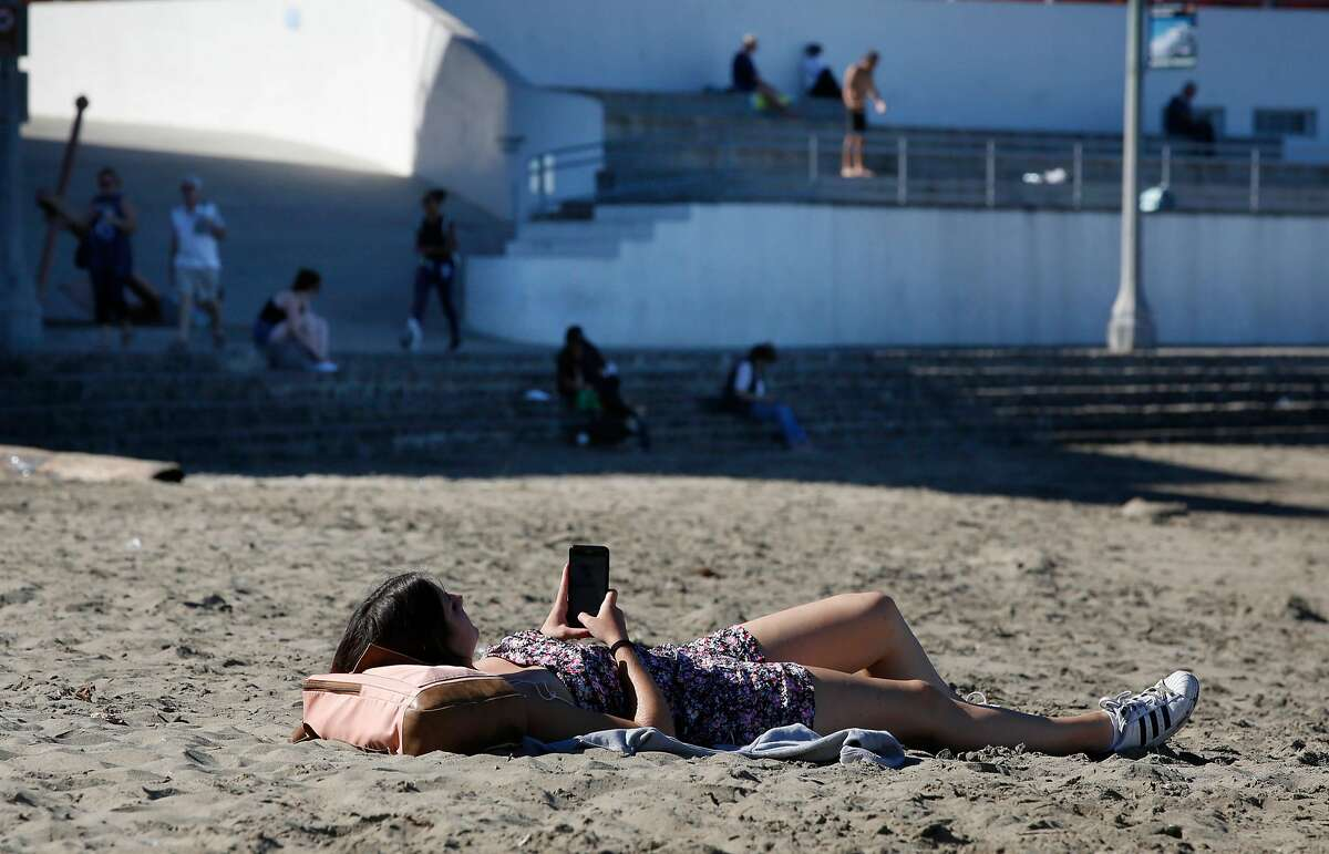 Lou Menin (foreground) checks her phone as she lays in the sun on the beach while others enjoy the weather from the shade (background) at Aquatic Park on Tuesday, October 24, 2017 in San Francisco, Calif.