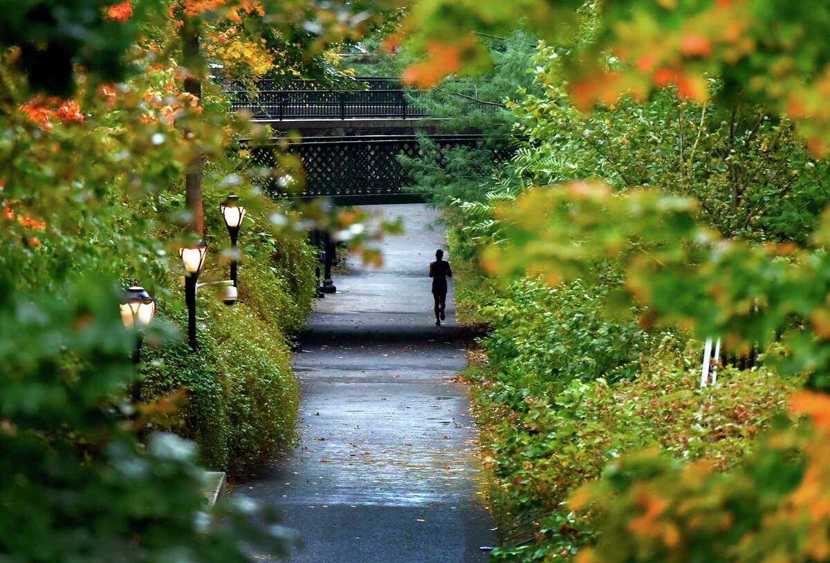 New Haven, Connecticut - Tuesday, October 24, 2017: A jogger runs past fall foliage and in between rain drops along the Farmington Canal Trail near Trumbull Street, Prospect Street and Canal Street in New Haven Tuesday afternoon.