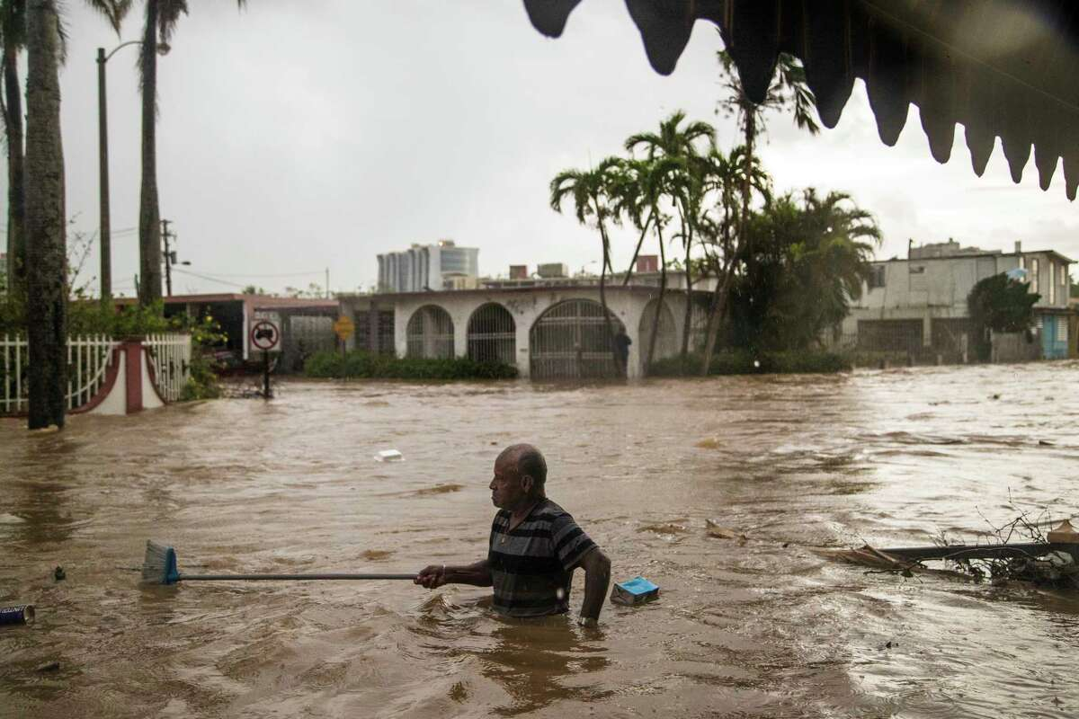 Maximiliano Encarnacion uses a broom to push away debris carried by the floodwaters caused by torrential rains on Oct. 8 in San Juan, 18 days after Hurricane Maria touched down in Puerto Rico.