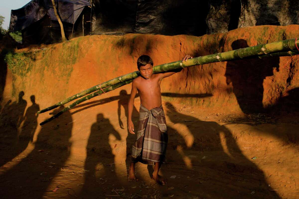 FILE - In this Oct. 23, 2017, file photo, a Rohingya Muslim boy, who crossed over from Myanmar into Bangladesh, carries bamboos given to him in aid for construction of shelter at Kutupalong refugee camp in Bangladesh. U.S. officials are preparing a recommendation for Secretary of State Rex Tillerson to declare that ethnic cleansing is occurring against MyanmarÂ?'s Rohingya Muslims. That assessment would raise pressure on the Trump administration and American lawmakers to consider new sanctions on a country that had been lauded for its democratic transition. (AP Photo/Dar Yasin, File)