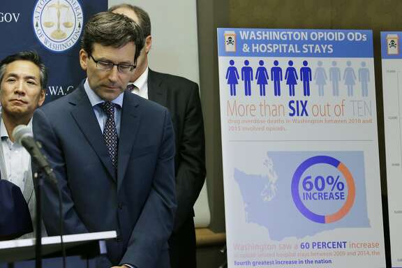 Washington Attorney General Bob Ferguson, second from left, listens to a question, Thursday, Sept. 28, 2017, in Seattle, as he stands near a chart detailing increases in overdoses and hospital stays relating to opioid use in Washington state. Ferguson said Thursday that the state and the city of Seattle are filing lawsuits against several makers of opioids, including Purdue Pharma, seeking to recoup costs incurred by government when the drugs -- which many officials blame for a national addiction crisis -- are abused. (AP Photo/Ted S. Warren)