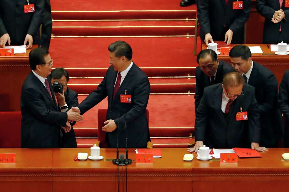 Chinese President Xi Jinping, center, shakes hands with former President Hu Jintao as former President Jiang Zemin, is assisted to stand during the closing ceremony for the Party Congress. Photo: Andy Wong, STF / Copyright 2017 The Associated Press. All rights reserved.