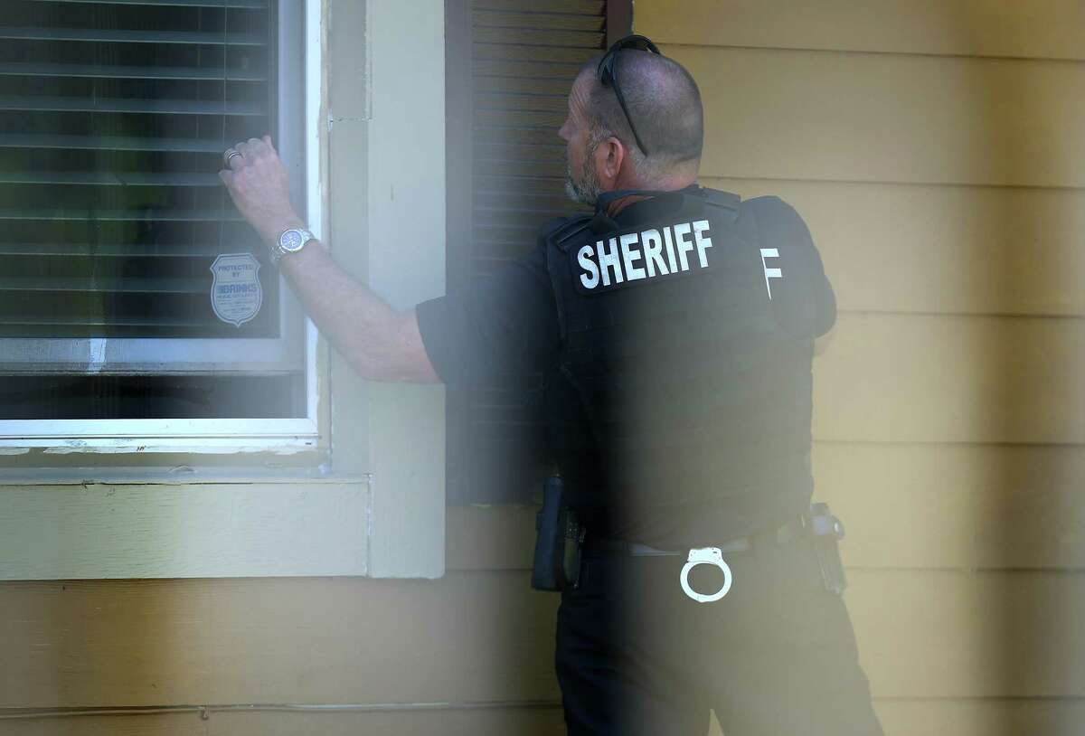 Harris County Sheriff's Office deputy Don Bock knocks on a window of a home while serving a warrant for a suspect, facing two counts of sexual assault and one count of felony criminal mischief Tuesday, Oct. 24, 2017, in Houston.