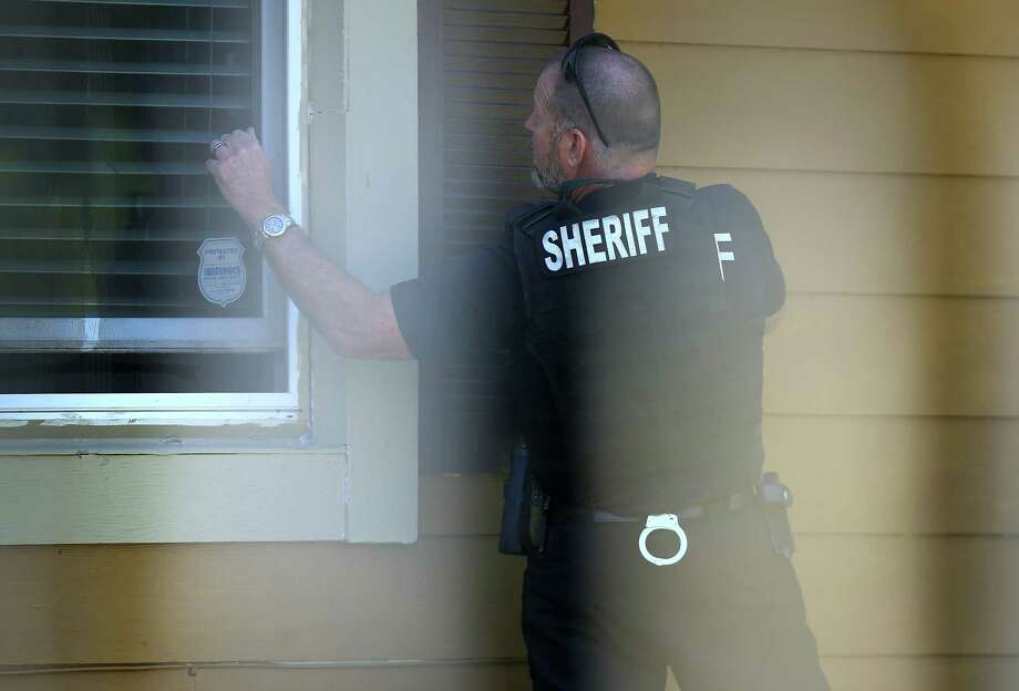 Harris County Sheriff's Office deputy Don Bock knocks on a window of a home while serving a warrant for a suspect, facing two counts of sexual assault and one count of felony criminal mischief Tuesday, Oct. 24, 2017, in Houston. Photo: Godofredo A. Vasquez, Houston Chronicle / Godofredo A. Vasquez