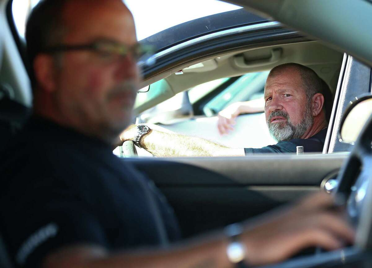 Harris County Sheriff's Office deputies Thom Smith, foreground, and Don Bock discuss a warrant for a suspect with two counts of sexual assault and one count of felony criminal mischief Tuesday, Oct. 24, 2017, in Houston.