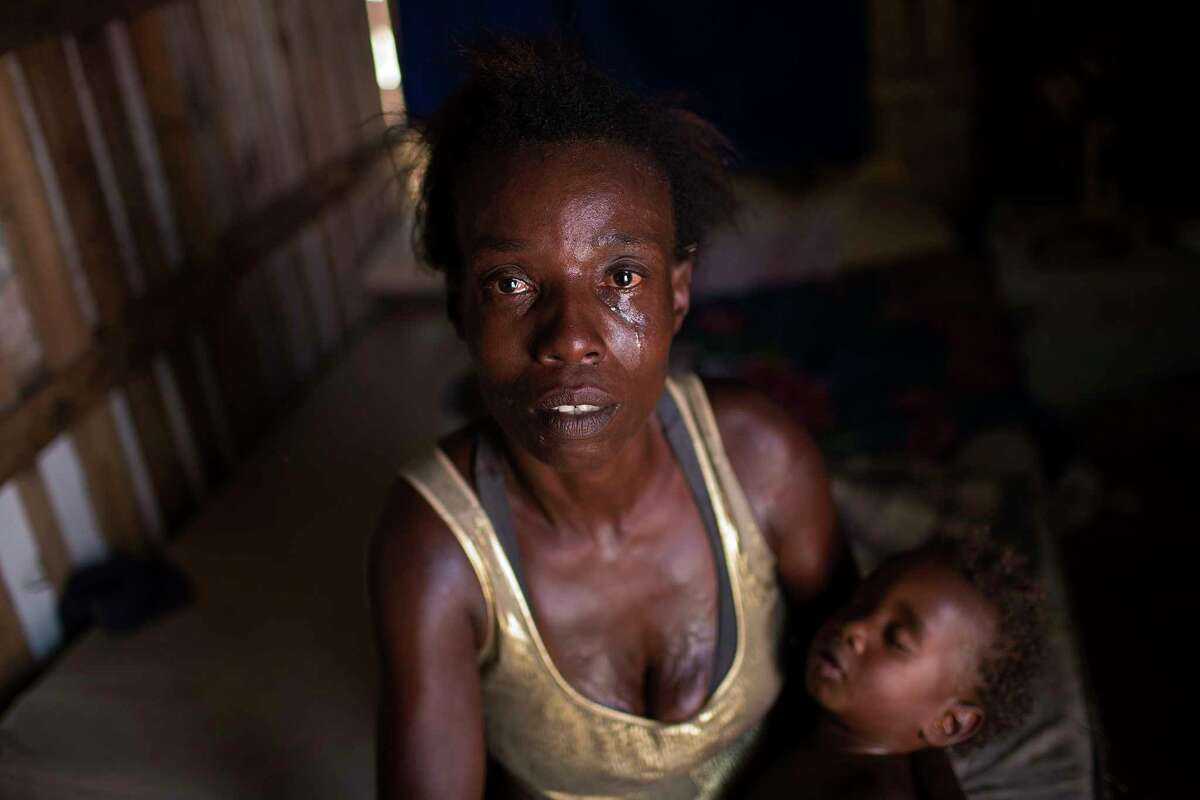 """In this Oct. 20, 2017 photo, Simone Batista, holding her baby Arthur, looks into the camera as tears roll down her cheeks while she recounts being cut from the """"Bolsa Familia"""" government subsidy program for low-income people, at her shack home in the Jardim Gramacho slum of Rio de Janeiro, Brazil. Batista wants to appeal the government cutting her from the program, but doesn't have enough money to take buses to the administrative office downtown. (AP Photo/Silvia Izquierdo)"""