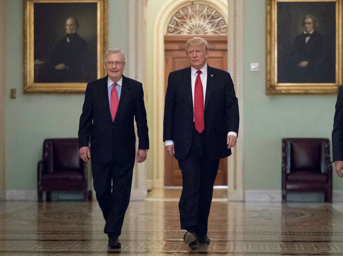 President Donald Trump, escorted by Senate Majority Leader Mitch McConnell, R-Ky., left, arrives on Capitol Hill to have lunch with Senate Republicans and push for his tax reform agenda Tuesday. (AP Photo/J. Scott Applewhite)