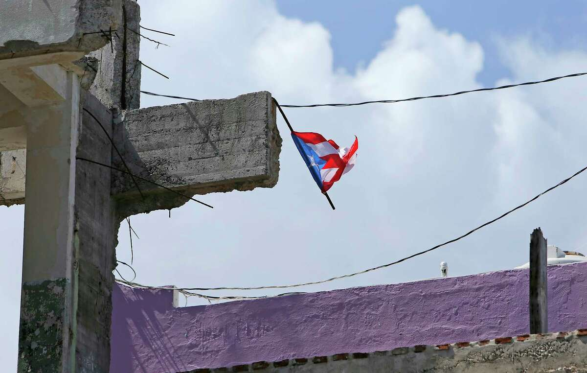 A Puerto Rican flag flies over the ruins of a building hit by Hurricane Maria in San Juan.