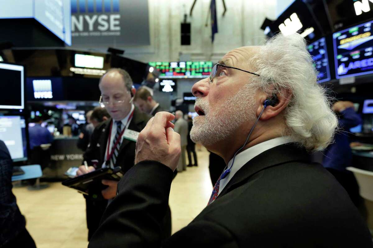 Trader Peter Tuchman, right, works on the floor of the New York Stock Exchange, Tuesday, Oct. 24, 2017. U.S. stocks are edging higher Tuesday morning as construction equipment maker Caterpillar and Post-it note maker 3M lead a rally in industrial companies, while banks are climbing along with interest rates. (AP Photo/Richard Drew)