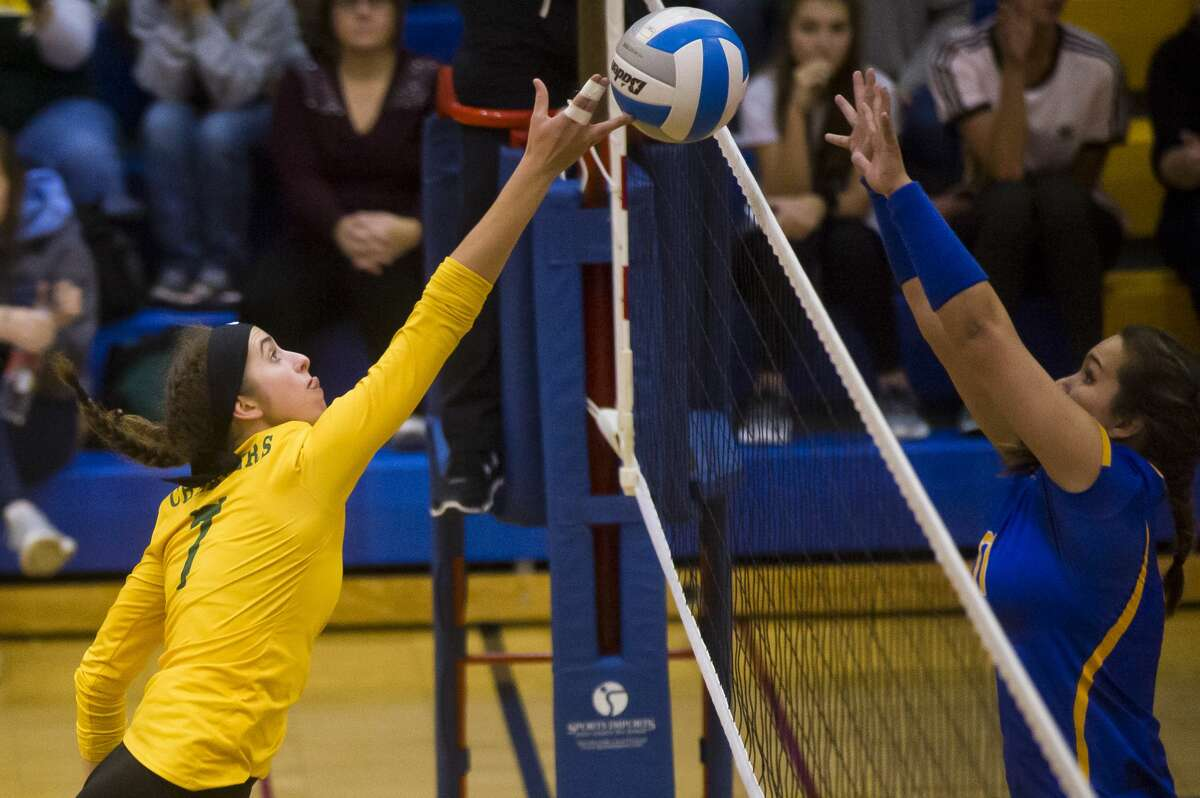 Dow sophomore Hailey Tanis tips the ball over the net as Midland senior Alexandria McMath defends during their match on Tuesday, Oct. 24, 2017 at Midland High. (Katy Kildee/kkildee@mdn.net)