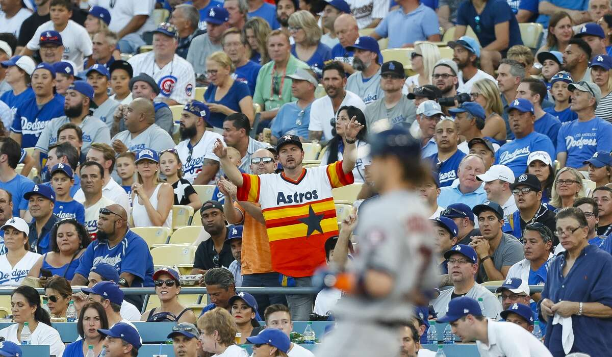 An Astros fan cheers among a sea of Los Angeles fans during the third inning of Game 1 of the World Series at Dodger Stadium on Tuesday, Oct. 24, 2017, in Los Angeles. ( Brett Coomer / Houston Chronicle )