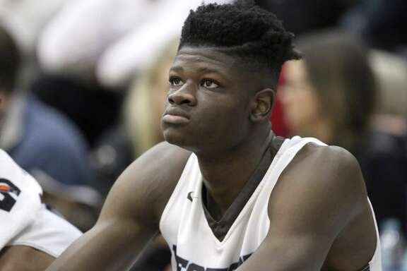 FILE - In this Jan. 14, 2017, file photo, Westtown School's Mo Bamba watches from the bench during a high school basketball game against Hillcrest Prep at the 2017 Hoophall Classic in Springfield, Mass. The older brother of Texas basketball recruit Mo Bamba, one of the top incoming players in the country next season, says Bamba took improper gifts and money from a Detroit financial adviser that would make him ineligible to play in college. Texas says Bamba's amateur status had previously been reviewed by the NCAA and he's been cleared to play (AP Photo/Gregory Payan, File)