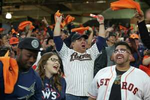 Chris Varela, center, celebrates Tuesday at a World Series watch party in Minute Maid Park after Astros third baseman Alex Bregman hits a home run.