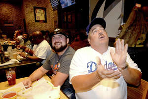 Michael Thibodeaux and his father Stephen Thibodeaux, a long-time Dodgers fan, react as Astro's fans gather to cheer on the team during game 1 of the World Series Tuesday at Buffalo Wild Wings. Photo taken Tuesday, October 24, 2017 Kim Brent/The Enterprise
