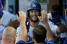 Los Angeles Dodgers pitcher Clayton Kershaw is greeted with high-fives in the dugout after a succesful third-inning sacrifice bunt against the Houston Astros in Game 1 of the World Series at Dodger Stadium in Los Angeles on Tuesday, Oct. 24, 2017. The Dodgers won, 3-1. (Robert Gauthier/Los Angeles Times/TNS)