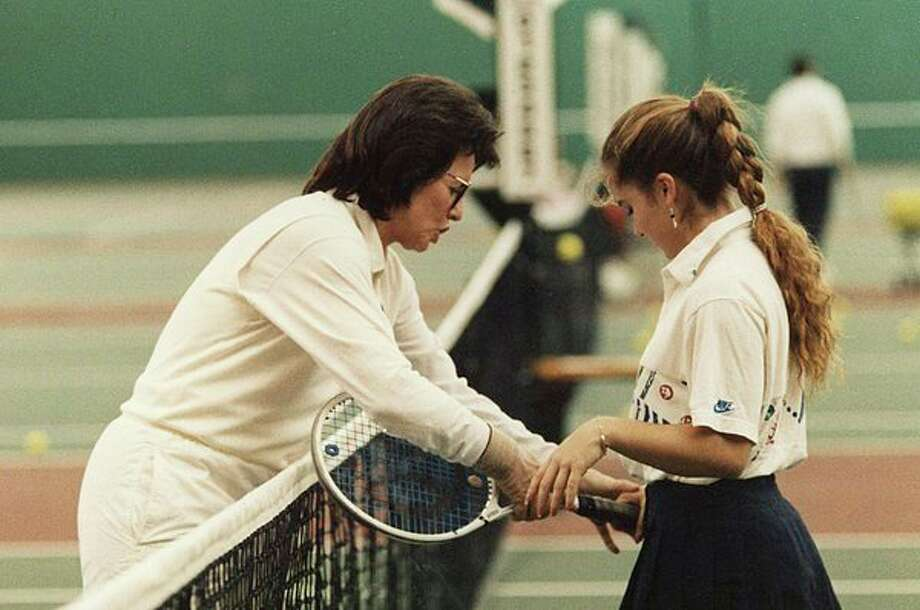 Billie Jean King helps a young tennis player during her visit to the Greater Midland Tennis Center in 1990. (Photo by Tom Gulvas)
