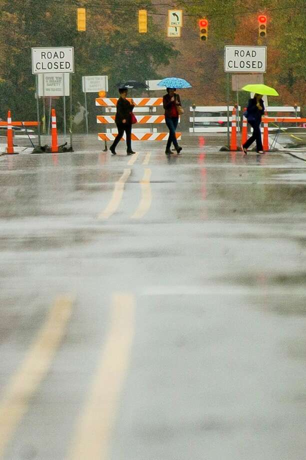 People walk across Main Street carrying umbrellas on Monday. The Tittabawassee River is expected to crest at about 1 p.m. Wednesday at 20 feet, 4 feet below flood stage. As of 1:15 p.m. Monday, the river was at 10 feet. (Katy Kildee/kkildee@mdn.net)