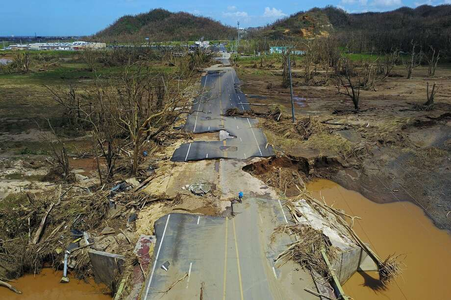 A man rides his bicycle through a damaged road in Toa Alta, west of San Juan. Photo: Ricardo Arduengo / AFP / Getty Images