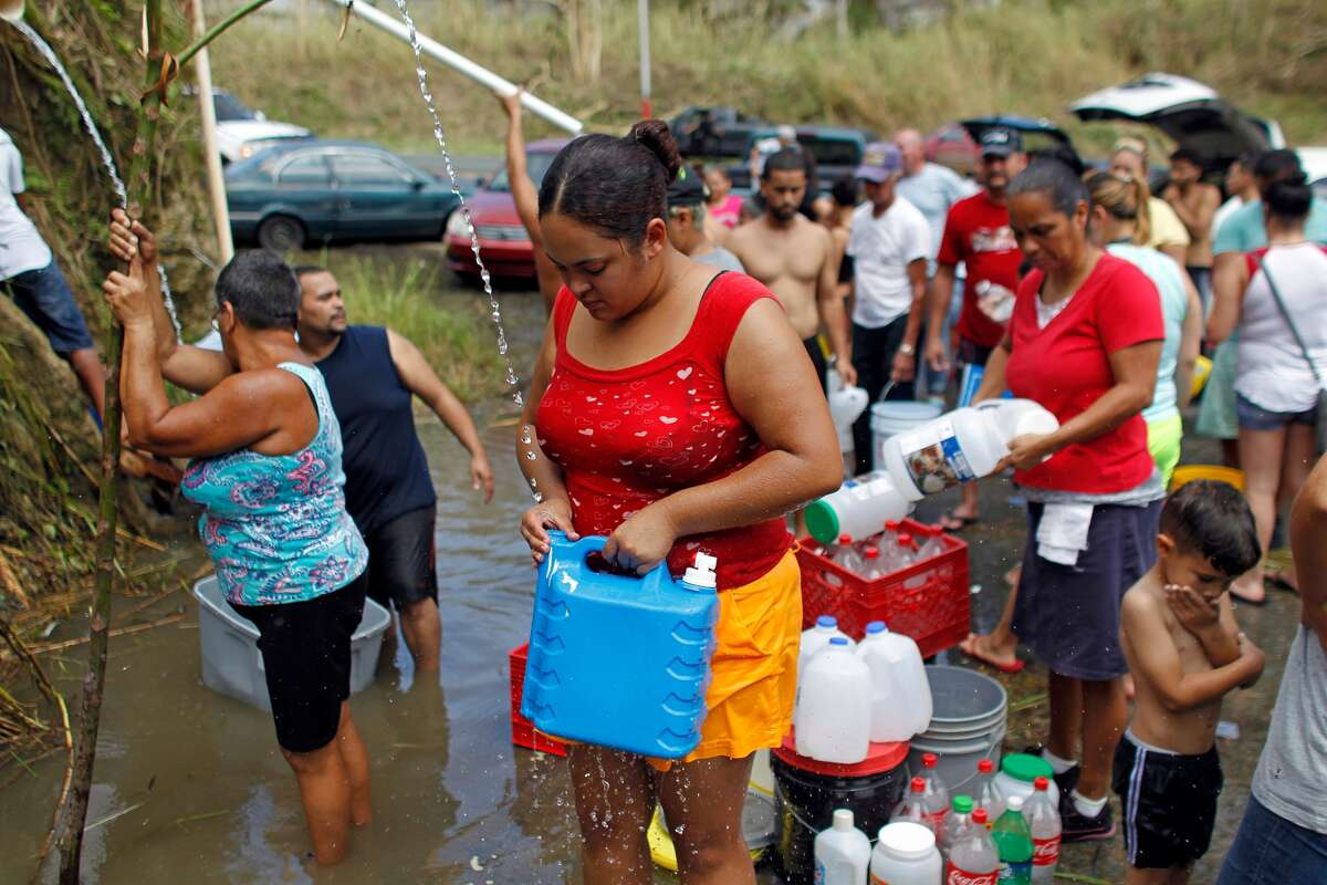 People collect water from a natural spring created by the landslides in a mountain next to a road in Corozal, west of San Juan, Puerto Rico, on September 24, 2017 following the passage of Hurricane Maria.HPD police officers are leaving Thursday to go assist Puerto Rican police.