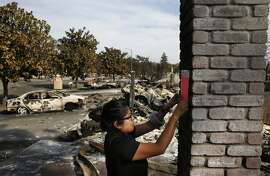 Cecilia Sevilla, Building Inspector with the Safety Assessment Program, Cal Office of Emergency Services posts signs in the wreckage of homes declaring them inhabitable in the Coffey neighborhood Oct. 17, 2017 in Santa Rosa, Calif.