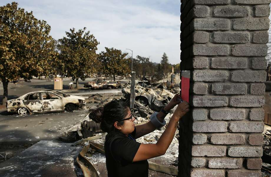 Cecilia Sevilla, building inspector with the Safety Assessment Program of the state Office of Emergency Services posts signs in the wreckage of homes declaring them inhabitable in the Coffey neighborhood Oct. 17, 2017 in Santa Rosa, Calif. Photo: Leah Millis, The Chronicle