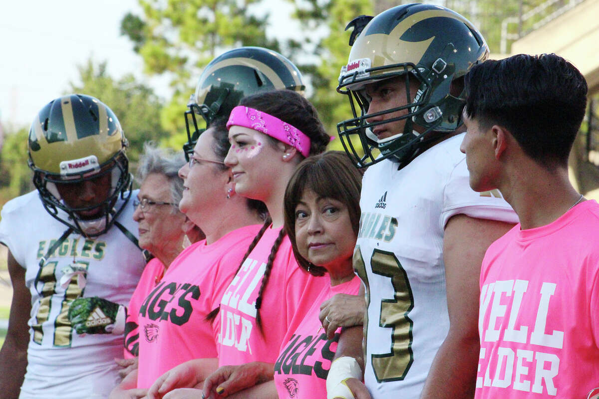 Marta Imelda Martinez (center) looks to her left before she and fellow breast cancer survivors and fighters were honored before a football game Oct. 7 between Cypress Falls and Cypress Springs high schools at Cy-Fair FCU Stadium. Martinez was escorted during the pregame ceremony by her grandson and Cypress Falls football player Tristan Garcia (second from right).
