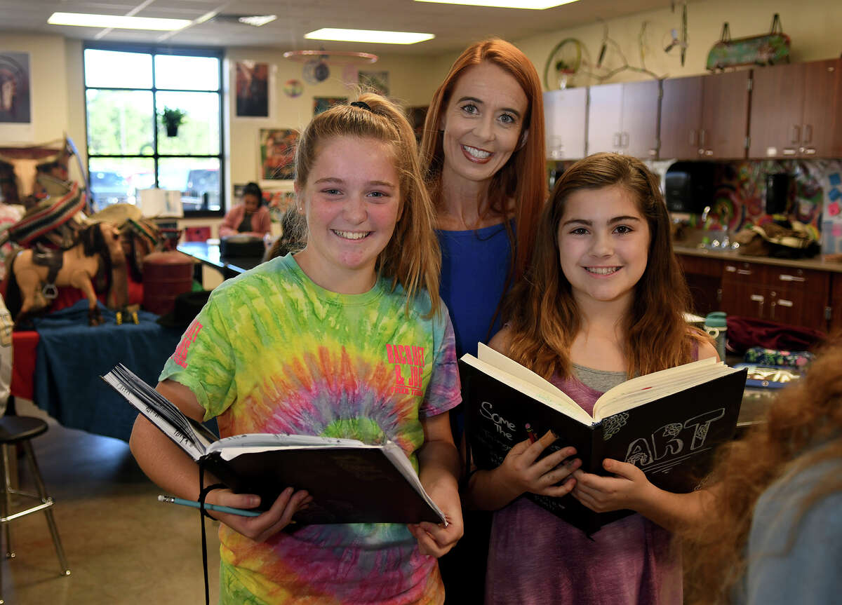 Faith Underwood, 11, left, and Peyton Bishop, 11, right, both Creekside Park Junior High 6th graders, share their sketch books with Tomball ISD Principal Partner Dawn Rodriguez, center, during their Art I class at CPJH on Oct. 24, 2017. (Photo by Jerry Baker/Freelance)