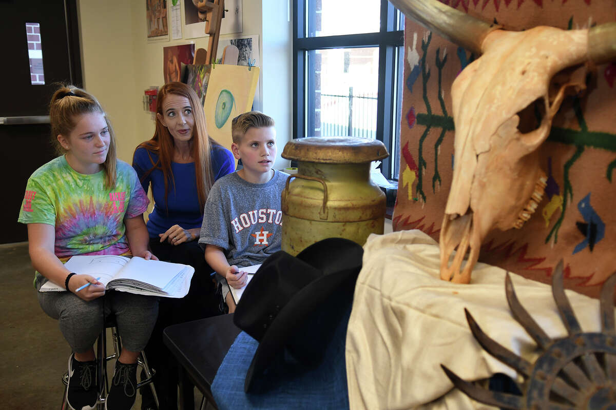 Faith Underwood, 11, left, and Malcolm Kerr, 11, right, both Creekside Park Junior High 6th graders, show off their drawing skills to Tomball ISD Principal Partner Dawn Rodriguez, center, during their Art I class at CPJH on Oct. 24, 2017. (Photo by Jerry Baker/Freelance)