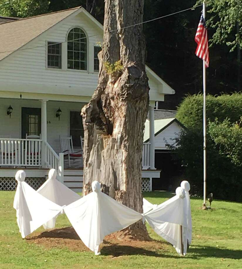 "There's been a bit of a buzz about the spirited activity happening on River Road in Washington lately. In the spirit of Halloween, Debbee and Frank Tomczyk constructed a display of ghosts holding hands and dancing around a large tree in their yard. Debbee said she saw a similar design in South Britain and ""thought it was adorable."" Using white sheets she bought at a tag sale, ghost heads she purchased at a local craft store, and tomato stakes, the couple created the six ghosts in their front yard. The display has drawn quite a bit of attention, according to Debbee, who said motorists stop to take photographs of the ghosts on their way to Steep Rock. Photo: Courtesy Of Diana Hardee / The News-Times Contributed"
