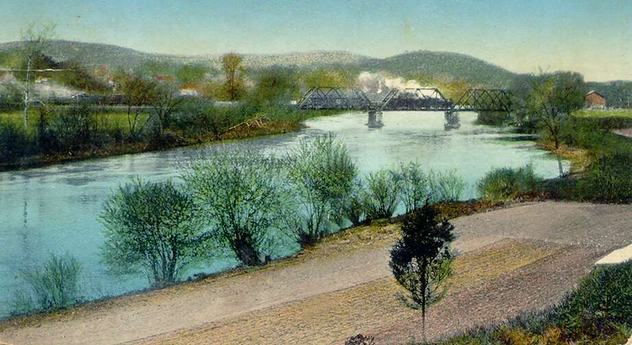 "Depicted in this old postcard photo by P.M. Cassedy, published in Germany of a train crossing the railroad bridge spanning the Housatonic River, just south of the village center in New Milford,. In the foreground is the east bank of the Housatonic where lower Grove Street now serves as a major thoroughfare for area residents. The postcard was sent Aug. 1, 1911 by Nonnie to Mr. Albert Manion, South Street, Danbury, Conn. Nonnie writes: ""Just a card to say goodbye. I suppose you met E.T.L. Now don't forget we expect to see you in Lynchville in the near future. Nonnie"" If you have a ""Way Back When"" photograph you'd like to share, contact Deborah Rose at 860-355-7324 or drose@newstimes.com. Photo: Courtesy Of Helen Cherney / The News-Times Contributed"