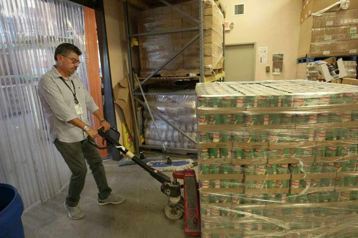 Jesse Mendoza, 62, moves a stack of canned food at the Second Mile Mission Center.