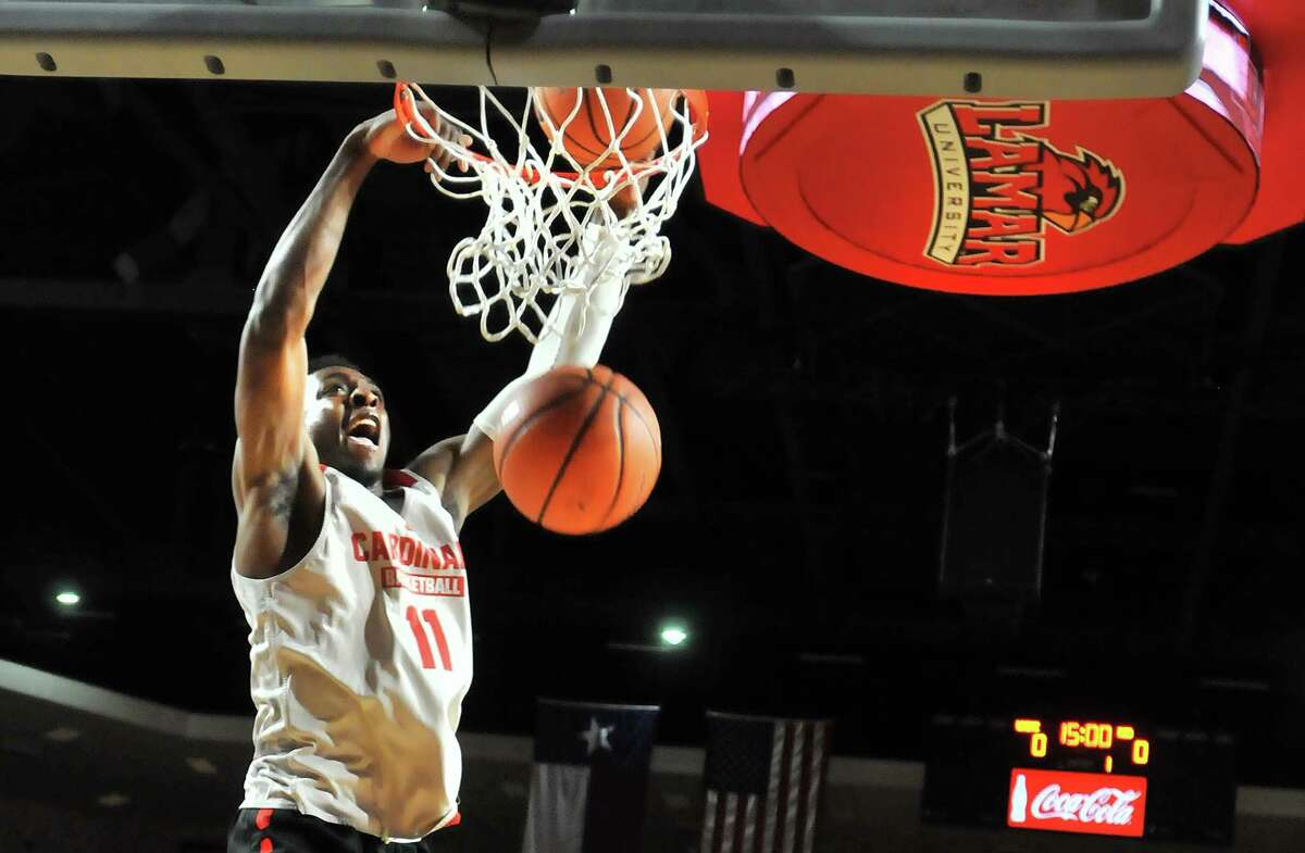 Lamar's Josh Nzeakor stuffs two balls into the basket during the slam dunk contest at the Cardinals' Big Red Madness event Tuesday at the Montagne Center. (Mike Tobias/The Enterprise)